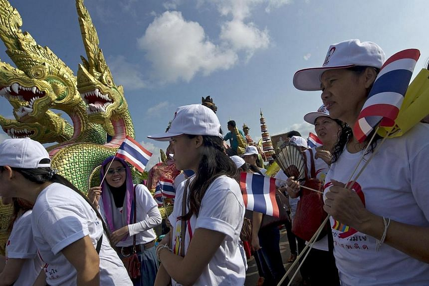 Thai workers hold national flags as they parade to mark May Day in Bangkok on May 1, 2014. -- PHOTO: AFP