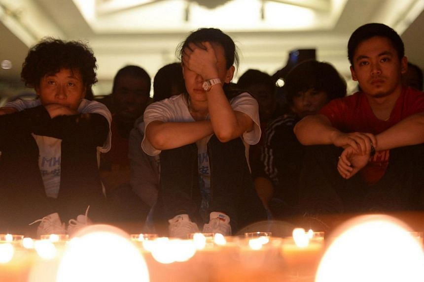 Chinese relatives of passengers on the missing Malaysia Airlines flight MH370 pray by candles at the Metro Park Hotel in Beijing on April 8, 2014.Malaysia Airlines (MAS) has asked family members of passengers on board missing flight MH370 to re