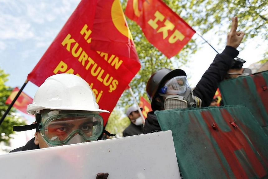 Protesters hold makeshift shields ahead of a May Day demonstration in central Istanbul on May 1, 2014. Tens of thousands of people across the globe were hitting the streets on Thursday, April 30, 2014, for mass rallies marking International Labour Da