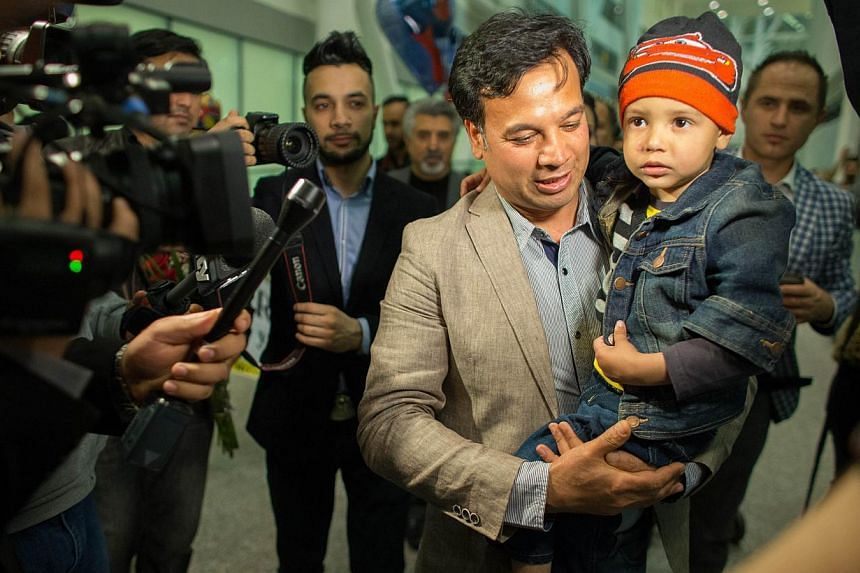 Mr Bashir Mirzad holds his nephew Abuzar Ahmad as he is greeted by nearly 100 family and well wishers at Pearson Airport in Toronto on  April 30, 2014. -- PHOTO: AFP