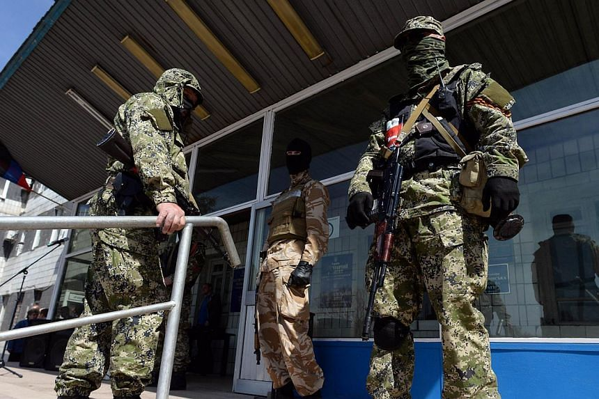 Pro-Russian armed men in military fatigues stand guard outside a regional administration building seized in the night by pro-Russian separatists, in the eastern Ukrainian city of Konstantinovka, on April 28, 2014. -- FILE PHOTO: AFP