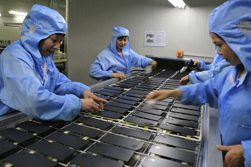 Workers processing laptop accessories at a factory in Dazu, Chongqing Municipality, April 22, 2014. -- FILE PHOTO: REUTERS