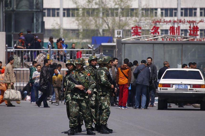 Paramilitary policemen stand guard near the exit of the South Railway Station, where three people were killed and 79 wounded in a bomb and knife attack on Wednesday, in Urumqi, Xinjiang Uighur Autonomous region, on May 1, 2014. A bombing in western C