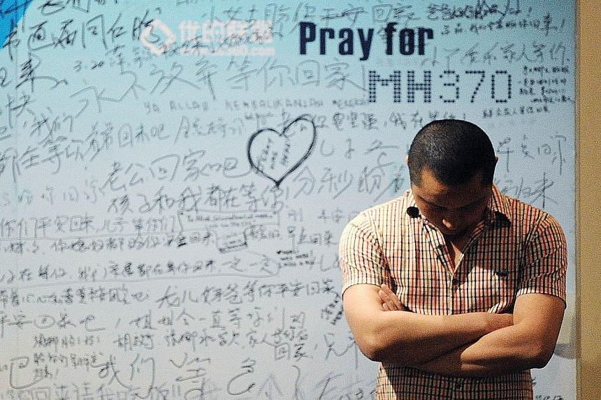 A man stands in front of a billboard in support of missing Malaysia Airlines flight MH370 as Chinese relatives of passengers on the missing Malaysia Airlines flight MH370 have a meeting at the Metro Park Hotel in Beijing on April 23, 2014. -- FILE PH