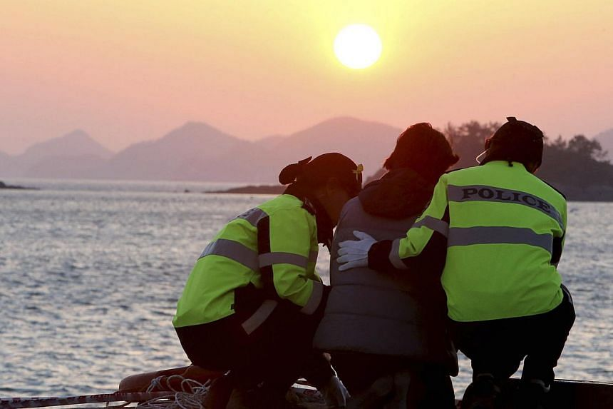 Policewomen comfort a family member (centre) of missing passengers onboard the capsized passenger ship Sewol, as she waits for news from a search and rescue operation team at a port in Jindo on April 30, 2014. -- PHOTO: REUTERS