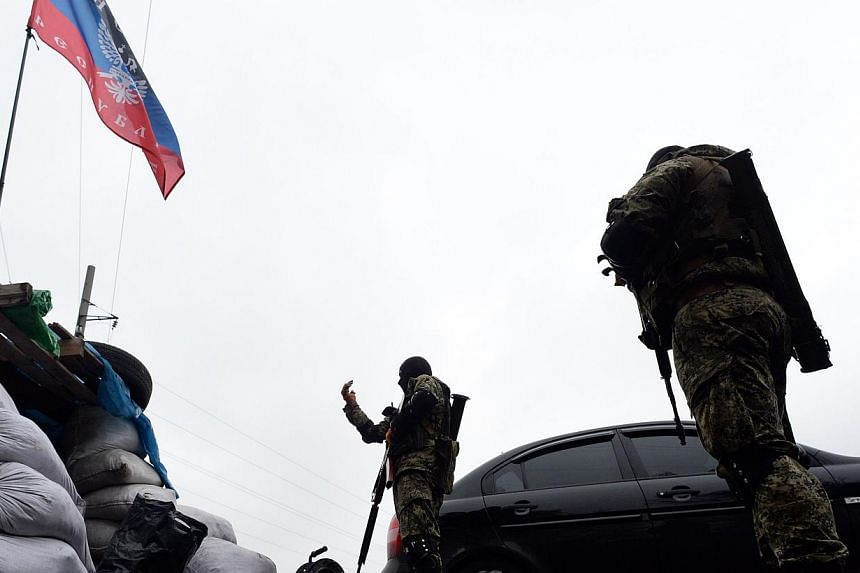 Armed pro-Russian activists stand guard at a checkpoint near the south eastern Ukrainain city of Slavyansk on April 30, 2014. -- PHOTO: AFP