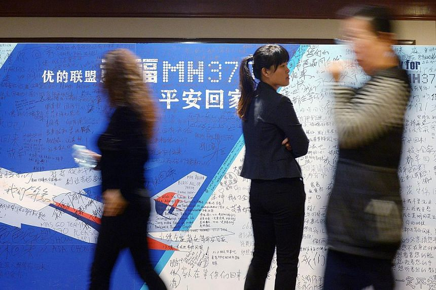 People walk past a billboard in support of missing Malaysia Airlines flight MH370 as Chinese relatives of passengers on the missing Malaysia Airlines flight MH370 have a meeting at the Metro Park Hotel in Beijing on April 23, 2014. Officials from Mal