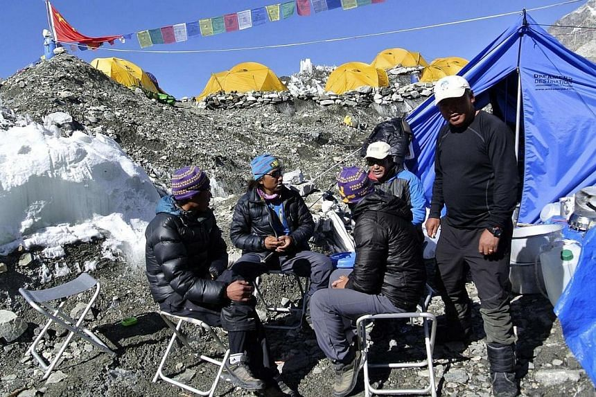 Sherpas sit at the base camp after a Mount Everest expedition was cancelled in Solukhumbu district on April 27, 2014.The recent death of 16 Sherpas in an avalanche on Mount Everest has brought inconsolable grief to their loved ones. -- FILE PHO