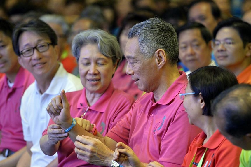 """PM Lee putting on an NTUC """"Better Energy Band"""" with the help of wife Ho Ching, during the official opening of the Devan Nair Institute for Employment and Employability yesterday. At left are Manpower Minister Tan Chuan-Jin and labour chief Lim Swee S"""