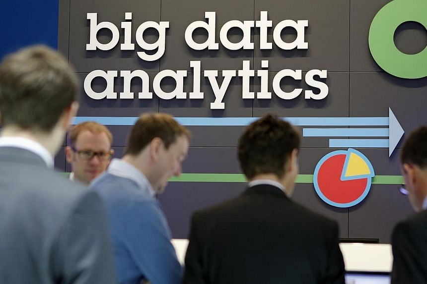 People stand in front of a big data analytics logo at the booth of IBM during preparations for the CeBIT trade fair in Hanover, on March 9, 2014. A study ordered by United States President Barack Obama and released May 1, 2014, concludes that analysi