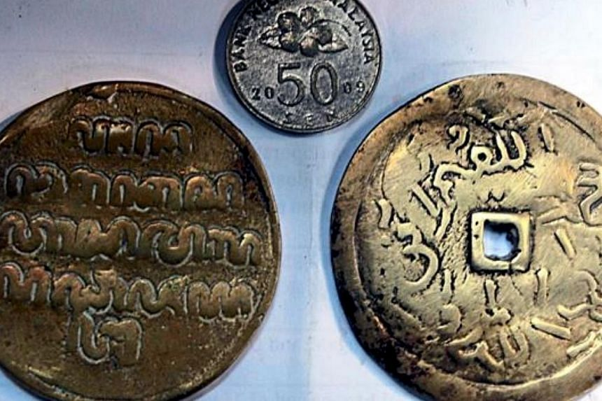 Workers of a salvaging company were said to have discovered two copper medallions, believed to be part of the billion ringgit wealth buried in the tiny island from the time of the Malacca Sultanate. -- PHOTO: THE STAR/ASIA NEWS NETWORK
