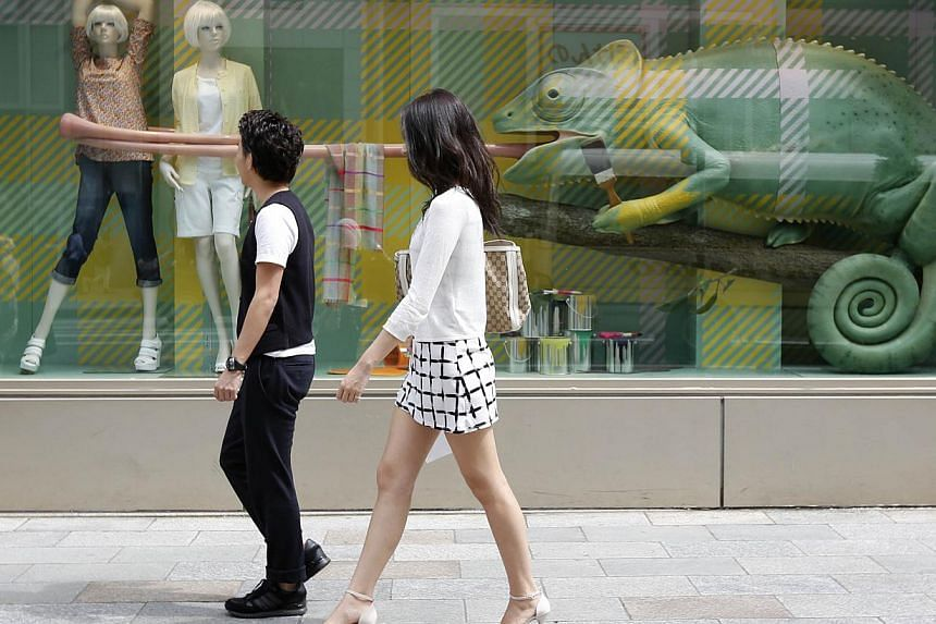 People walk past a display window of a clothing retail store at Ginza shopping district in Tokyo on April 28, 2014. -- FILE PHOTO: REUTERS