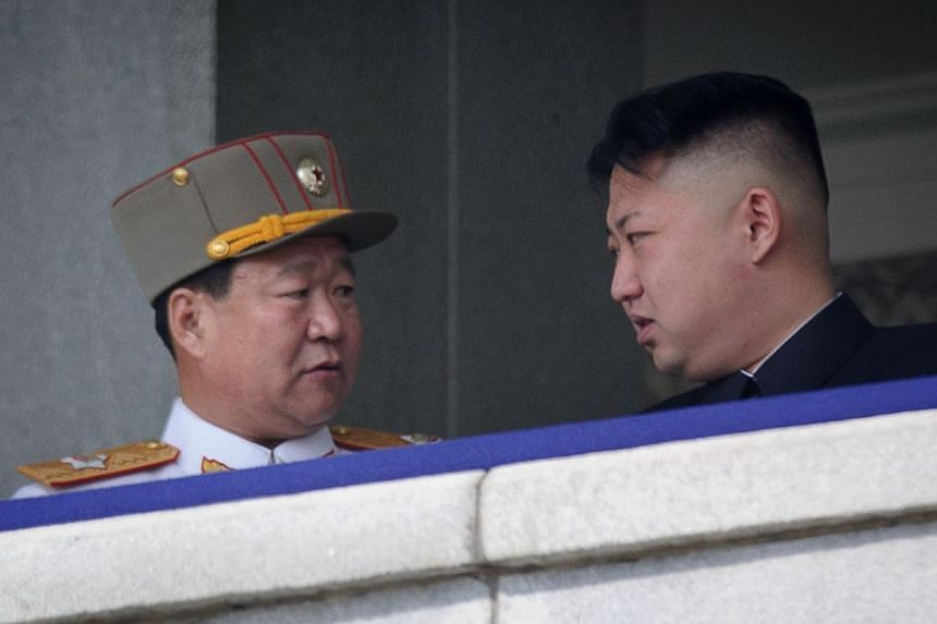 A photo taken on April 15, 2013 shows a man believed to be Choe Ryong-Hae talking with North Korean leader Kim Jong Un attending a military parade in Pyongyang. North Korea signalled a key leadership change with the announcement May 2, 2014 that the