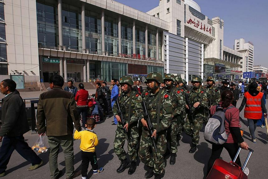 Armed policemen patrol near the exit of the South Railway Station, where three people were killed and 79 wounded in Wednesday's bomb and knife attack, in Urumqi, Xinjiang Uighur Autonomous region, on May 2, 2014. China's foreign ministry has reacted