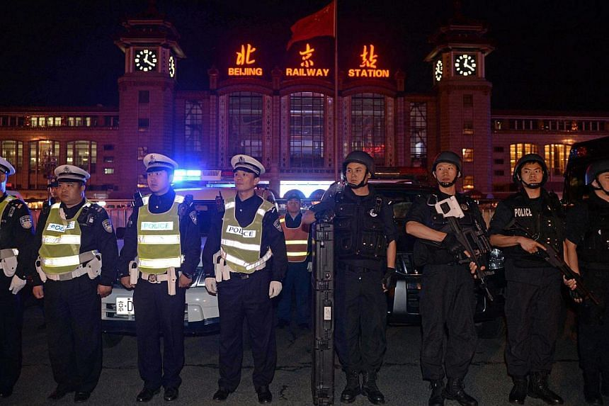 """Chinese policemen take up position during a drill outside the railway station in Beijing on the early hours of May 2, 2014. Beijing police said on Friday they held an """"anti-terror"""" drill at a rail station, a day after a deadly bombing in China's far"""