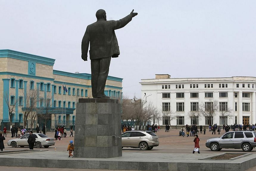 People walk near a statue of Soviet state founder Vladimir Lenin during Navruz celebrations in Baikonur, the town constructed to service the Baikonur Cosmodrome, on March 22, 2014. -- FILE PHOTO: REUTERS