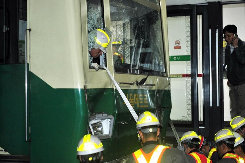 South Korean railway workers inspect a damaged train after a collision at Sangwangsimni station in Seoul on May 2, 2014. -- PHOTO: AFP