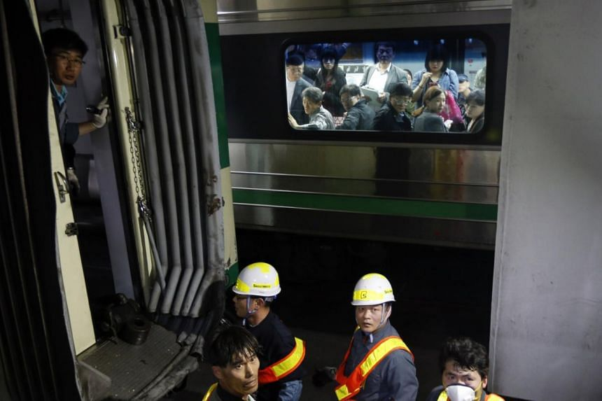 Passengers on the opposite side look at a damaged subway train as workers check it at a subway station in Seoul on May 2, 2014. -- PHOTO: REUTERS