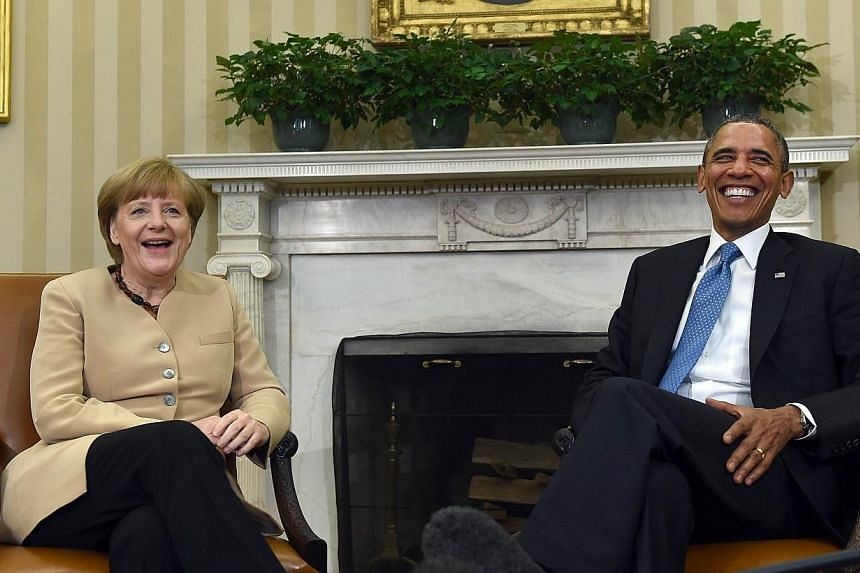 US President Barack Obama and German Chancellor Angela Merkel share a laugh before a bilateral meeting in the Oval Office at the White House on May 2, 2014 in Washington, DC. President Barack Obama welcomed Germany's Angela Merkel to the White House