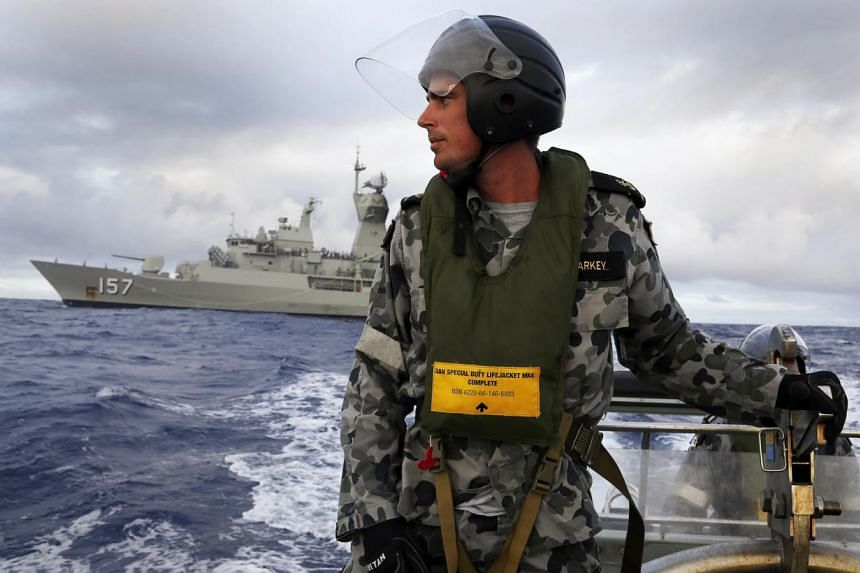 Standing in a rigid hull inflatable boat launched from the Australian Navy ship HMAS Perth, a seaman searches for possible debris from the missing Malaysia Airlines flight MH370 in the southern Indian Ocean on April 17, 2014. The first funeral servic