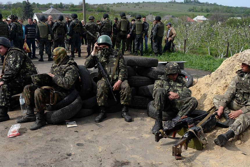 Ukrainian soldiers sit at checkpoint they seized in the early morning in the village of Andreevka, 7kms from the centre of the southern Ukrainian city of Slavyansk, on May 2, 2014. Russia called an emergency meeting of the UN Security Council on Frid