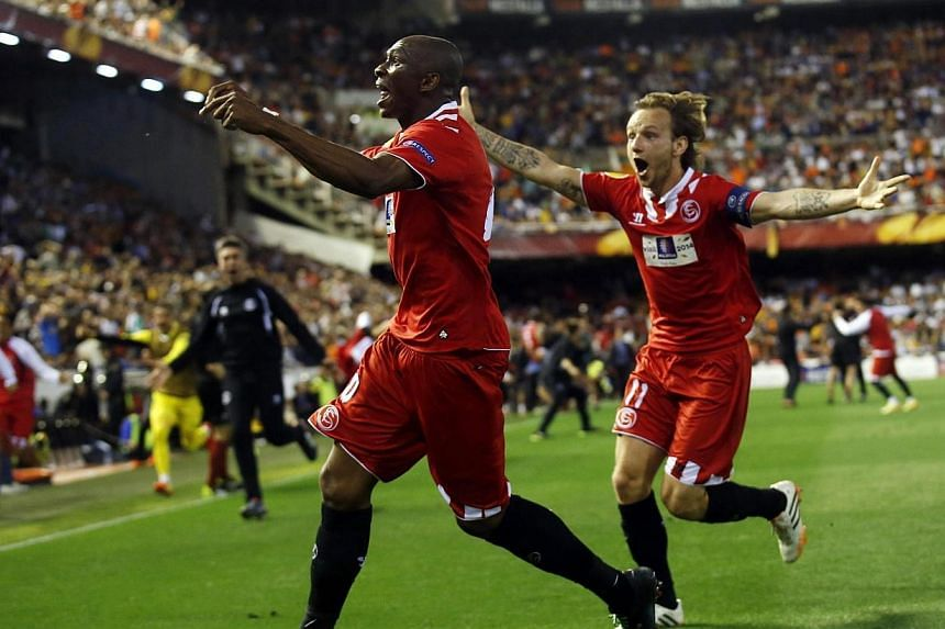 Sevilla's Stephane Mbia (left) and Ivan Rakitic celebrate Mbia's stoppage time goal against Valencia at the Mestalla stadium in Valencia on May 2, 2014. -- PHOTO: REUTERS