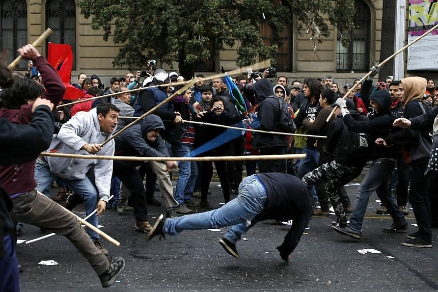 Pro-government communist (left) and anarchist (right) movement demonstrators clash during May Day demonstration in Santiago on May 1, 2014. -- PHOTO: REUTERS