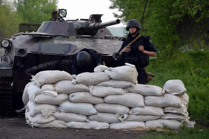 Ukrainian soldiers stand near a tank at a checkpoint near the south eastern Ukrainain city of Slavyansk on May 1, 2014. -- PHOTO: AFP