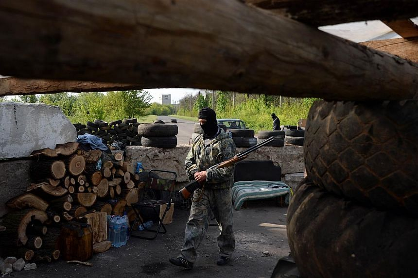 An armed pro-Russian activist stands guard at a checkpoint near the south eastern Ukrainain city of Slavyansk on May 1, 2014. -- PHOTO: AFP