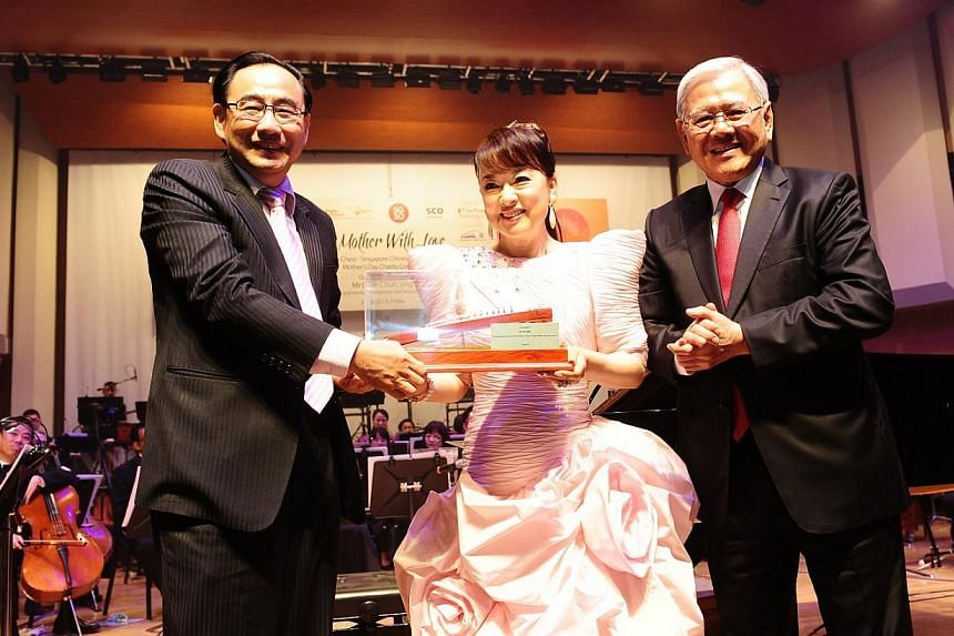 Community Chest Chairman Mr Phillip Tan (far left) presenting a token of appreciation to Ms Judy Ongg at the ComChest-SCO Mother's Day Charity Concert with the concert's adviser, Mr Poh Choon Ann.-- PHOTO: COMMUNITY CHEST