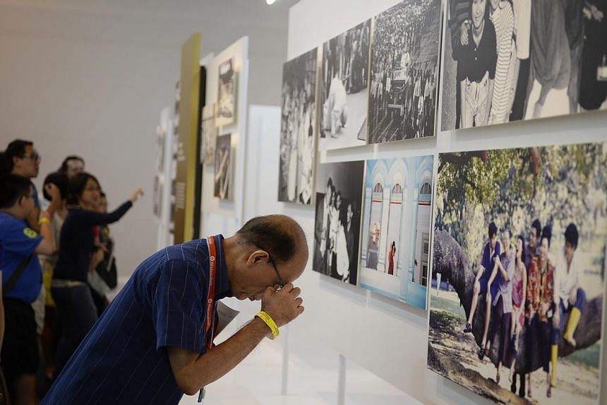 A man looks at picture captions during a tour of the exhibition called We: Defining Stories, presented by The Straits Times and the National Museum of Singapore, on 2 May, 2014. -- ST PHOTO: MARK CHEONG