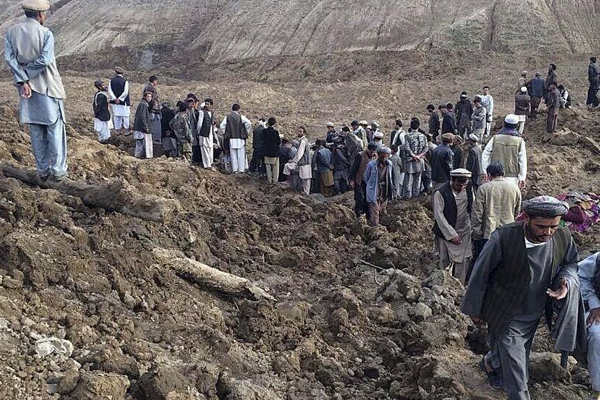 Afghan villagers gather at the site of a landslide at the Argo district in Badakhshan. More than 2,000 people are estimated to be trapped under the rubble in the remote mountainous area. -- PHOTO: REUTERS