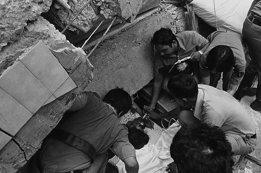 Rescue workers giving oxygen to a woman trapped in the rubble of the collapsed Hotel New World, 15 March, 1986. The six-storey hotel at Serangoon Road had collapsed like a house of cards earlier in the day at 11.26am. --ST PHOTO: FRANCIS ONG PUAY GUA