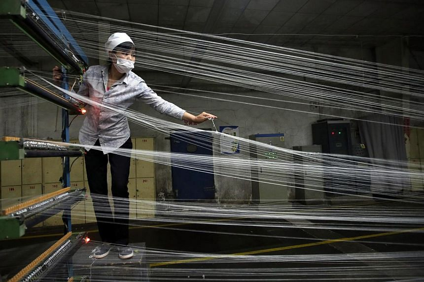 An employee works at a textile factory in Wuhan, Hubei province on April 30, 2014. Growth in China's services sector quickened slightly in April as the purchasing manufacturing index (PMI) for the industry edged up to 54.8 last month, government
