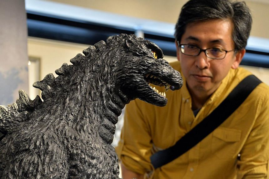 A Godzilla fan looks at a 1-metre tall statue at a Godzilla art exhibition in Tokyo on May 2, 2014. -- PHOTO: AFP