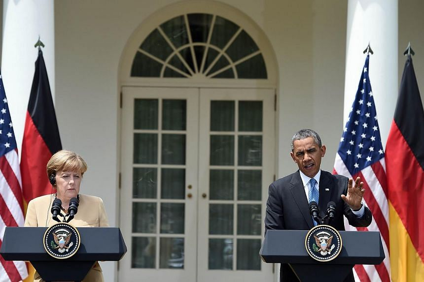 US President Barack Obama (right) answers a question as German Chancellor Angela Merkel listens during a press conference at the Rose Garden of the White House following their meeting on May 2, 2014 in Washington. MrObama and German Chancellor