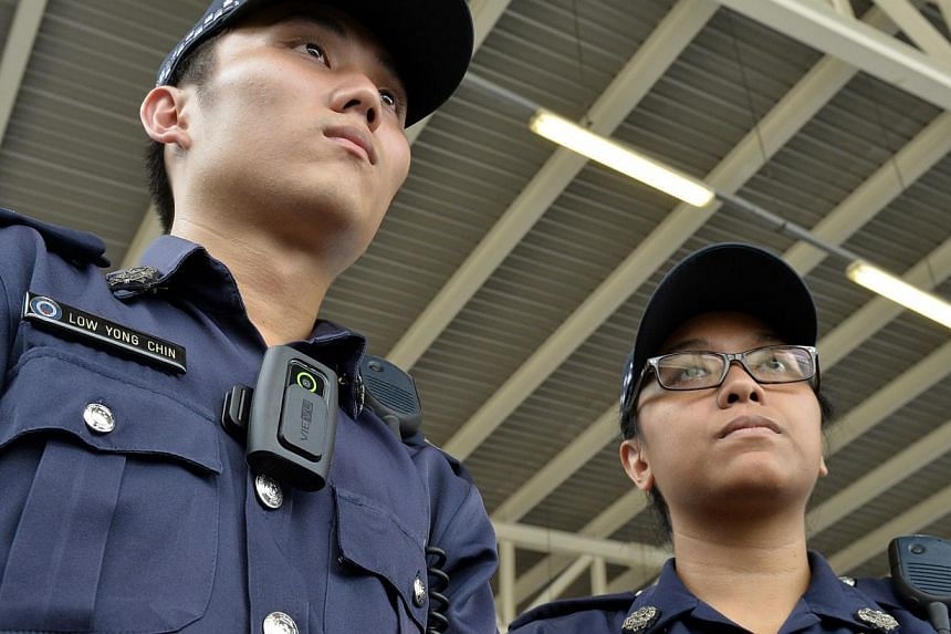 Two police officers with their Body-Worn Cameras (BWCs) which are useful devices for the SPF to record what officers see and hear during incidents. -- ST PHOTO: DESMOND FOO