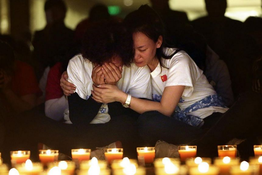 A family member cries as she and other relatives pray during a candlelight vigil for passengers onboard the missing Malaysia Airlines Flight MH370 in the early morning at Lido Hotel in Beijing on April 8, 2014. -- PHOTO: REUTERS