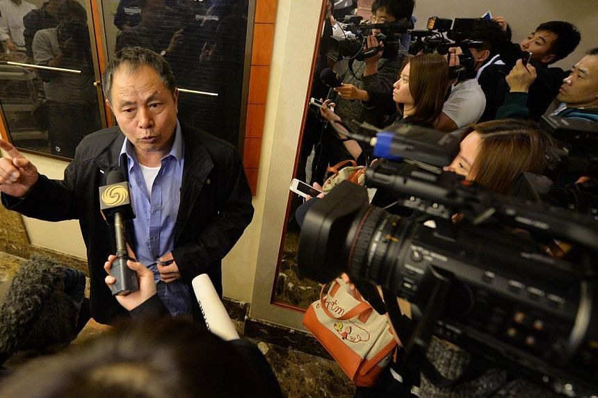Mr Wen Wancheng (L), whose son was on missing Malaysia Airlines flight MH370, speaks to the media after relatives met again with airline officials at the Metro Park Lido Hotel in Beijing on March 23, 2014. Mr Wen and his wife have gone home to their&