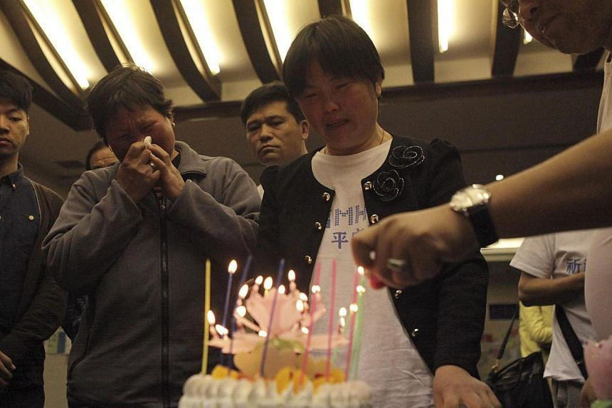 Family members cry as they light candles on a cake to mark the 21st birthday of a passenger onboard the missing Malaysia Airlines Flight MH370 at the Lido Hotel in Beijing on April 8, 2014. - PHOTO: REUTERS