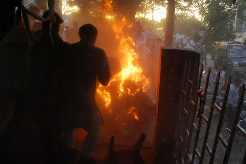Indian bystanders attempt to douse the blaze as local leader of the Bahujan Samaj Party, Mr Kamruzzama Fauji, and his attackerare engulfed in flames during an election television debate in a local park in Sultanpur, a town about 160km from the