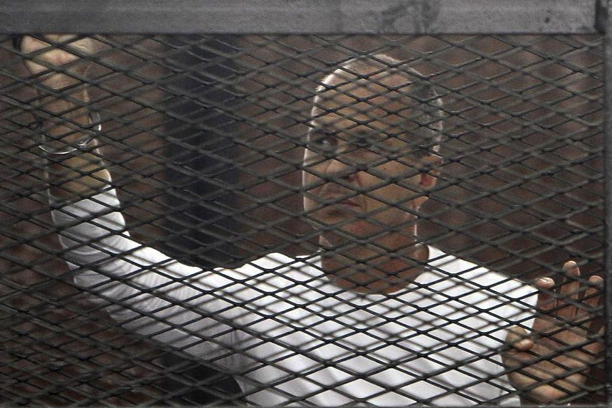 Al Jazeera journalist Peter Greste of Australia stands in a metal cage during his trial in a court in Cairo on March 24, 2014. An Australian journalist with satellite news channel al-Jazeera on trial in Egypt on Saturday, May 3, 2014, described his o