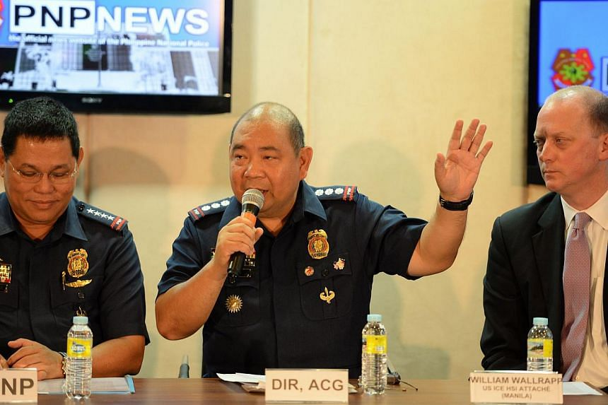 Philippine police chief of cyber crime division Gilbert Sosa (centre) answers questions from members of the media, while Philippine police chief Alan Purisima (left) and US ICE, HSI attache William Wallwrapp listen, during a press conferenc