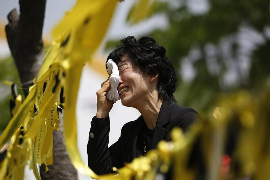 A mourner cries next to yellow ribbons dedicated to missing and dead passengers of sunken passenger ship Sewol, after paying tribute at the official memorial altar in Ansan on May 2, 2014. Eight more bodies were recovered on Saturday from the ferry t