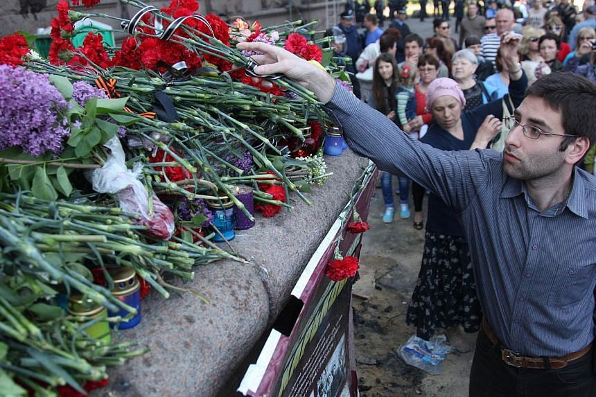 Pro-Russian activist lays flowers and candles to the burned trade union building in homage to the people who died yesterday in the southern Ukrainian city of Odessa on May 3, 2014. Ukraine's interim president on Saturday declared two days of mourning