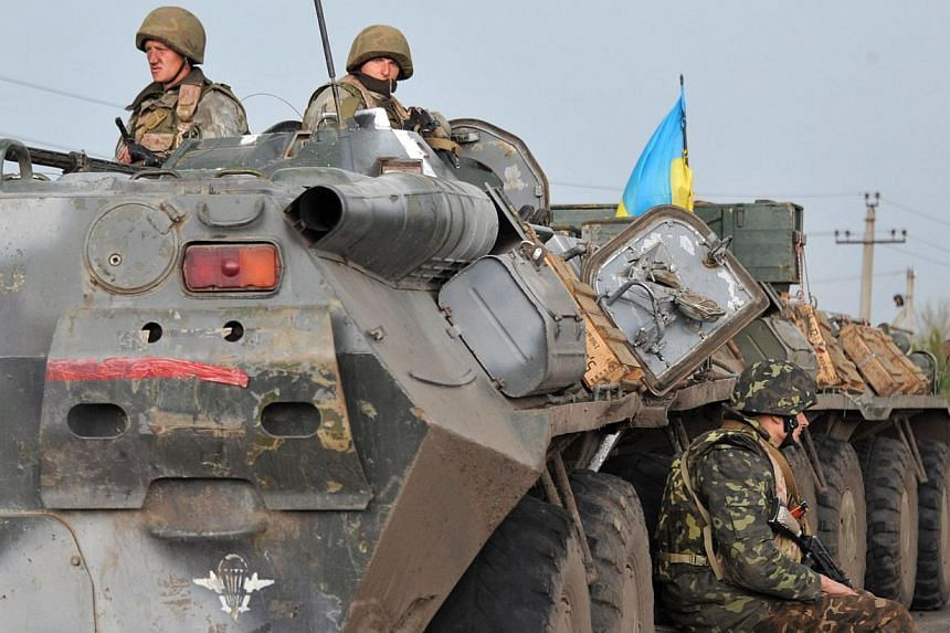 Ukrainian soldiers wait on the road as Pro-Russia separatists block the Kramators to Slavyansk road to prevent them from advancing on May 2, 2014. Ukraine's army on Saturday broadened a military offensive to retake control of rebel-held towns and cit
