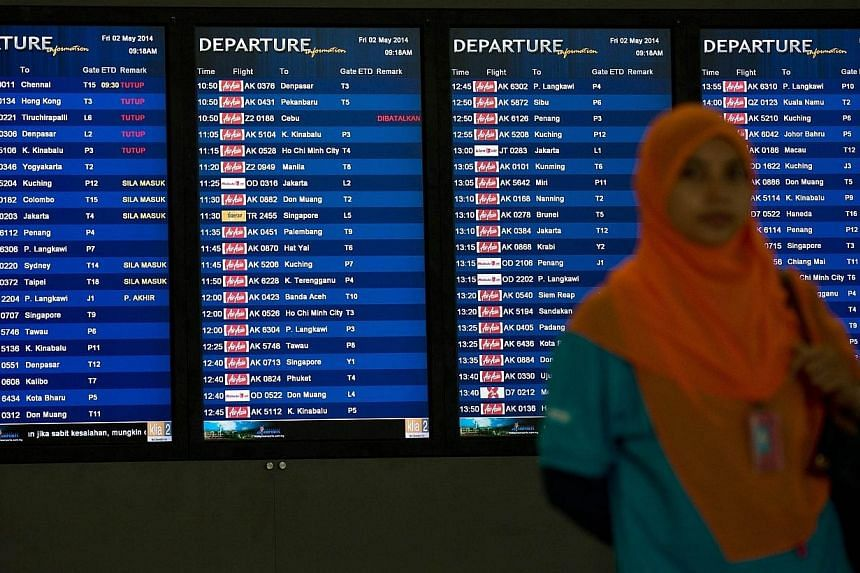 A woman stands in front of the flight information displays at the international departures of the low-cost carrier terminal at Kuala Lumpur International Airport 2 (KLIA2) in Sepang, outside Kuala Lumpur, on May 2, 2014. -- PHOTO: AFP