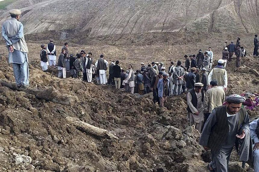 Afghan villagers gather at the site of a landslide at the Argo district in Badakhshan province on May 2, 2014. -- PHOTO: REUTERS