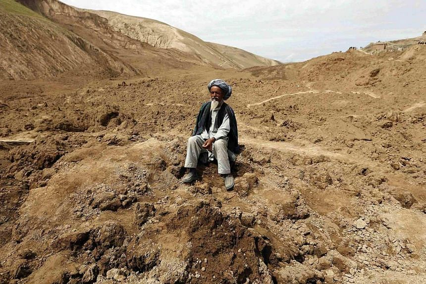 An Afghan man sits at the site of landslide at the Argo district in Badakhshan province on May 4, 2014. -- PHOTO: REUTERS