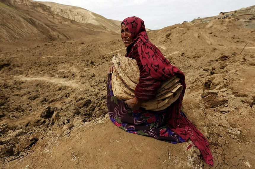 An Afghan woman cries after she lost her family in a landslide at the Argo district in Badakhshan province on May 4, 2014. -- PHOTO: REUTERS
